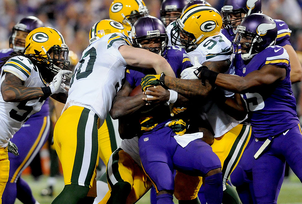 . Green Bay Packers inside linebacker A.J. Hawk , left, and defensive end Johnny Jolly stop Minnesota Vikings\' Adrian Peterson during the fourth quarter. (Pioneer Press: Sherri LaRose-Chiglo)