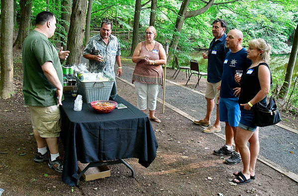 7/27/2019 Mike Orazzi | Staff Jason Pepin (left) descries beer from Firefly Hollow Brewing during the Hungerford Nature Center's Beer in the Woods event Saturday evening.