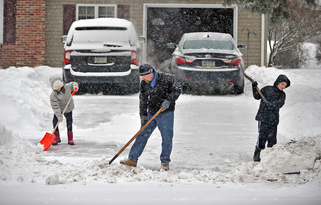 . Simon Tack and his children Marissa, 7, left, and Johnny, 9, shovel snow out of their driveway along Saxton Drive, in State College, Pa. on Thursday, Feb. 13, 2014. A winter storm hit Centre County causing all local schools to close amid dangerous travel conditions. (AP Photo/Centre Daily Times, Nabil K. Mark)