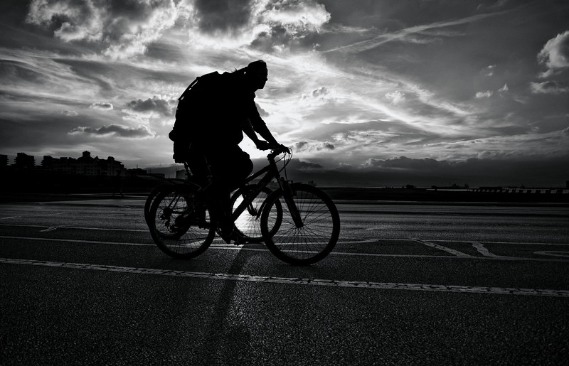 Cyclist crossing the runway of Gibraltar during sunset with deep clouds in the background. Street Photography and documentary image by Stephen Ignacio.