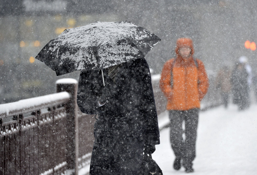 Description of . A pedestrian shields himself with an umbrella as he walks down the street on March 5, 2013 in Chicago, Illinois. The worst winter storm of the season is expected to dump 7-10 inches of snow on the Chicago area with the worst expected for the evening commute.  (Photo by Brian Kersey/Getty Images)