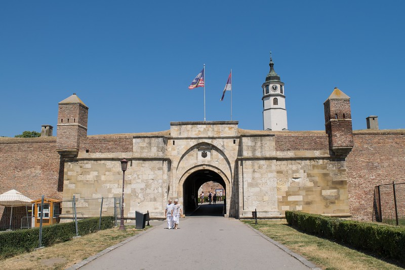 two people outside a castle gate with flags flying above