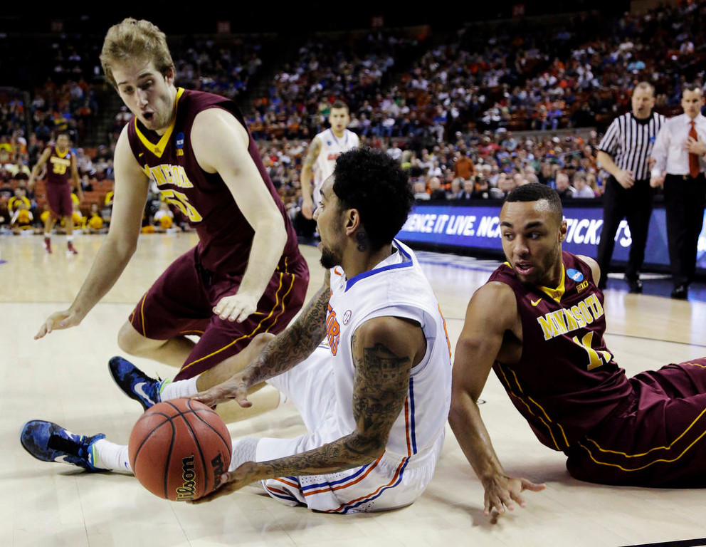 . Florida\'s Mike Rosario, center, reaches for a loose ball with Minnesota\'s Elliott Eliason, left, and Joe Coleman, right, during the first half of a third-round game of the NCAA college basketball tournament, Sunday, March 24, 2013, in Austin, Texas. (AP Photo/David J. Phillip)