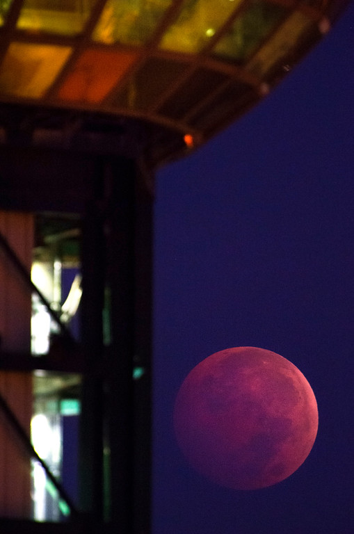 . A lunar eclipse dips beneath the Sunsphere in Knoxville, Tenn. on Wednesday, Oct. 8, 2014.  The moon appears orange or red, the result of sunlight scattering off Earth\'s atmosphere. This is known as the blood moon.(AP Photo/Knoxville News Sentinel, Adam Lau)