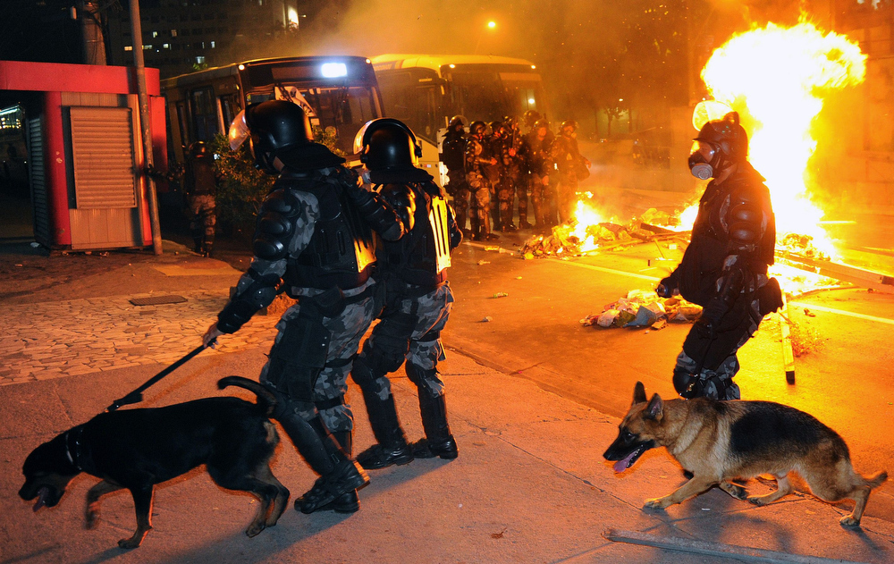 . Riot policemen walk next to a fire barricade in downtown Niteroi, near Rio de Janeiro, on June 19, 2013, during a protest against the $15 billion being spent on this month\'s Confederations Cup and the 2014 World Cup. Protests initially sparked by a hike in bus fares in Sao Paulo last week, quickly spiraled into nationwide marches against corruption, fueled by anger that -- in a country with a wide rich-poor divide -- billions of dollars were being spent on stadiums and far too little was earmarked for social programs.  TASSO MARCELO/AFP/Getty Images