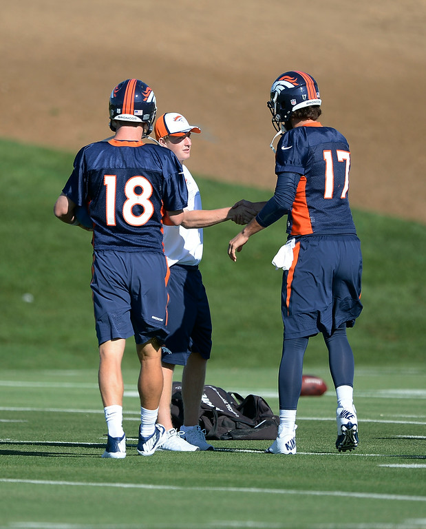 . Denver Broncos quarterback Brock Osweiler (17) and Denver Broncos quarterback Peyton Manning (18) shakes hands with Zander Ellis who is helping out with the quarterbacks during the Denver Broncos 2014 training camp July 24, 2014 at Dove Valley. (Photo by John Leyba/The Denver Post)