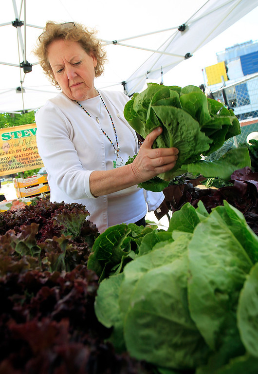 . Mary Irving checks out the various lettuce from Gilroy\'s Ground Stew Farms at the new Santa Clara Valley Medical Center Farmer\'s Market in San Jose, Calif. on Wednesday, May 15, 2013.  (LiPo Ching/Bay Area News Group)