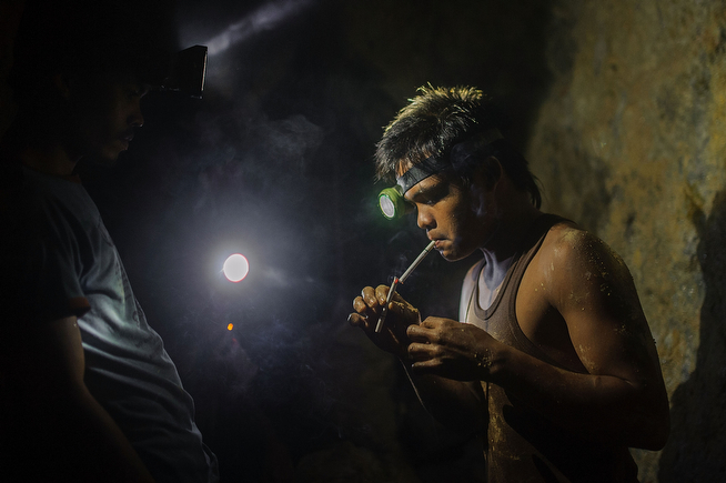 . A miner lights a Jackpot menthol cigarette from the tip of another. The miners smoke heavily in the tunnels, and the air is thick with second hand smoke. They exclusively smoke Jackpot menthols because they are cheaper and last longer than other cigarettes, on April 22, 2014 in Pinut-An, Philippines. (Photo by Luc Forsyth/Getty Images)