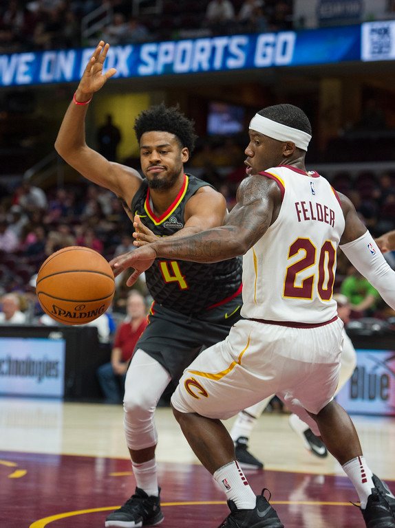 . Atlanta Hawks\' Quinn Cook (4) and Cleveland Cavaliers\' Kay Felder (20) go for a loose ball during the second half of an NBA preseason basketball game in Cleveland, Wednesday, Oct. 4, 2017. The Hawks won 109-93. (AP Photo/Phil Long)