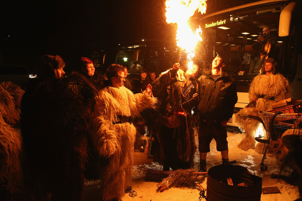 . Participants who arrived by bus and will be dressed as the Krampus creature watch a colleague spit fire prior to Krampus night on November 30, 2013 in Neustift im Stubaital, Austria. Sixteen Krampus groups including over 200 Krampuses participated in the first annual Neustift event. Krampus, in Tyrol also called Tuifl, is a demon-like creature represented by a fearsome, hand-carved wooden mask with animal horns, a suit made from sheep or goat skin and large cow bells attached to the waist that the wearer rings by running or shaking his hips up and down. Krampus has been a part of Central European, alpine folklore going back at least a millennium, and since the 17th-century Krampus traditionally accompanies St. Nicholas and angels on the evening of December 5 to visit households to reward children that have been good while reprimanding those who have not. However, in the last few decades Tyrol in particular has seen the founding of numerous village Krampus associations with up to 100 members each and who parade without St. Nicholas at Krampus events throughout November and early December.  (Photo by Sean Gallup/Getty Images)