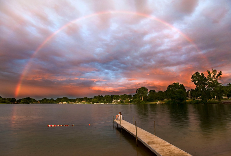Stacy Schnarr watches a rainbow at sunset in Whitmore Lake, 10 miles North of Ann Arbor, MI on June 21, 2012.  The Michigan summer in 2012 was one of the warmest and driest on record.