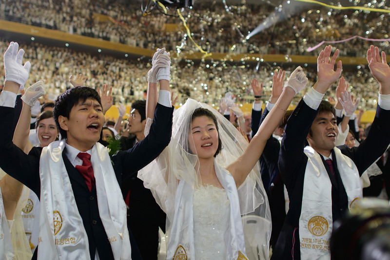 ". Couples celebrate during a mass wedding event held by the Unification Church in Gapyeong on February 12, 2014. Unification Church members forming 2500 couples from 52 countries were married in a mass wedding in South Korea -- only the second such event since the death of their ""messiah\"" and controversial church founder Sun Myung Moon. (ED JONES/AFP/Getty Images)"
