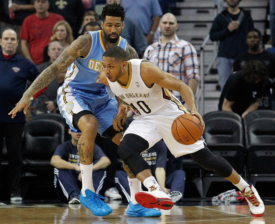 . New Orleans Pelicans shooting guard Eric Gordon (10) works around Denver Nuggets small forward Wilson Chandler in the first half of an NBA basketball game in New Orleans, Sunday, March 9, 2014. (AP Photo/Bill Haber)