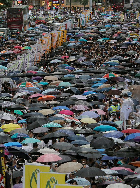 . People hold umbrellas while marching under the rain during an annual protest in downtown Hong Kong Tuesday, July 1, 2014. Hong Kong residents marched through the streets of the former British colony to push for greater democracy in a rally fueled by anger over Beijing\'s recent warning that it holds the ultimate authority over the southern Chinese financial center. The protest comes days after nearly 800,000 residents voted in a mock referendum aimed at bolstering support for full democracy. (AP Photo/Vincent Yu)