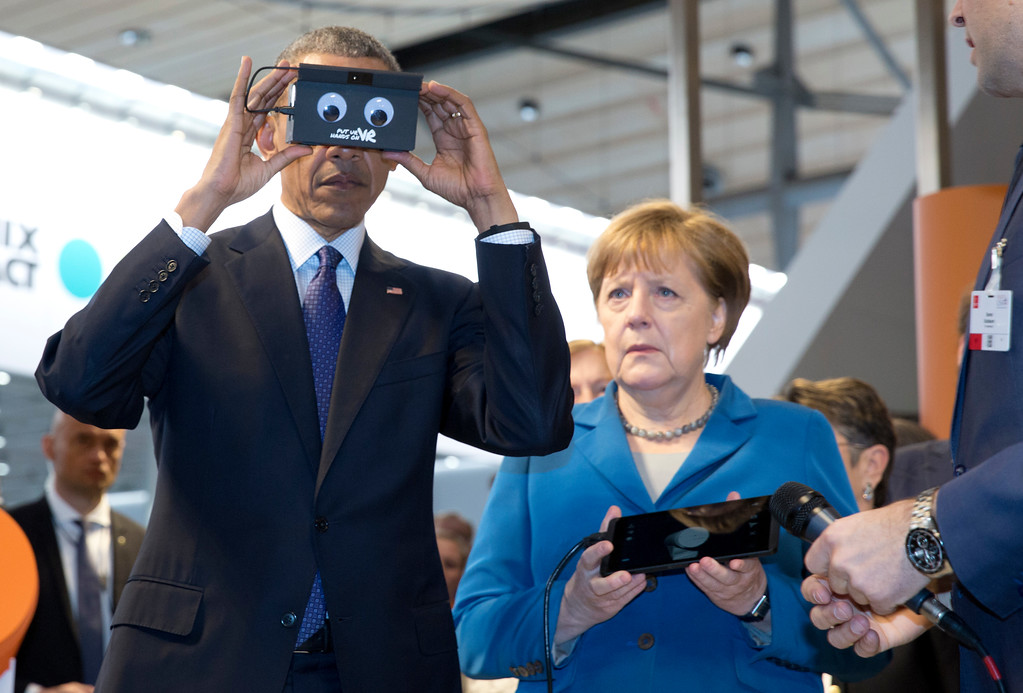 . German Chancellor Angela Merkel looks on as U.S President Barack Obama tests VR goggles when touring the Hannover Messe, the world\'s largest industrial technology trade fair, in Hannover, northern Germany, Monday, April 25, 2016. Obama is on a two-day official visit to Germany. (AP Photo/Carolyn Kaster)