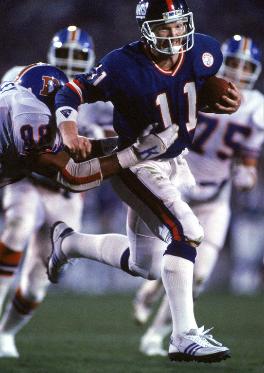 . Quarterback Phil Simms #11 of the New York Giants runs with the ball against the Denver Broncos during Super Bowl XXI at the Rose Bowl on January 25, 1987 in Pasadena, California.  (Photo by George Rose/Getty Images)