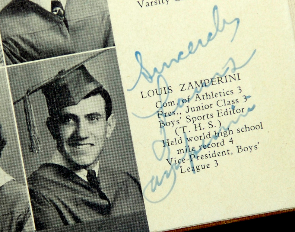 . TORRANCE - 01/27/07 - DAILY BREEZE PHOTO: SCOTT VARLEY - Torrance High and graduate Louis Zamperini celebrate their 90th birthdays Saturday at the school. 1935 graduate Julian Isen brough his yearbook with Zamerini\'s picture and signature. (1/27/07)  (Photo by Scott Varley/Daily Breeze)