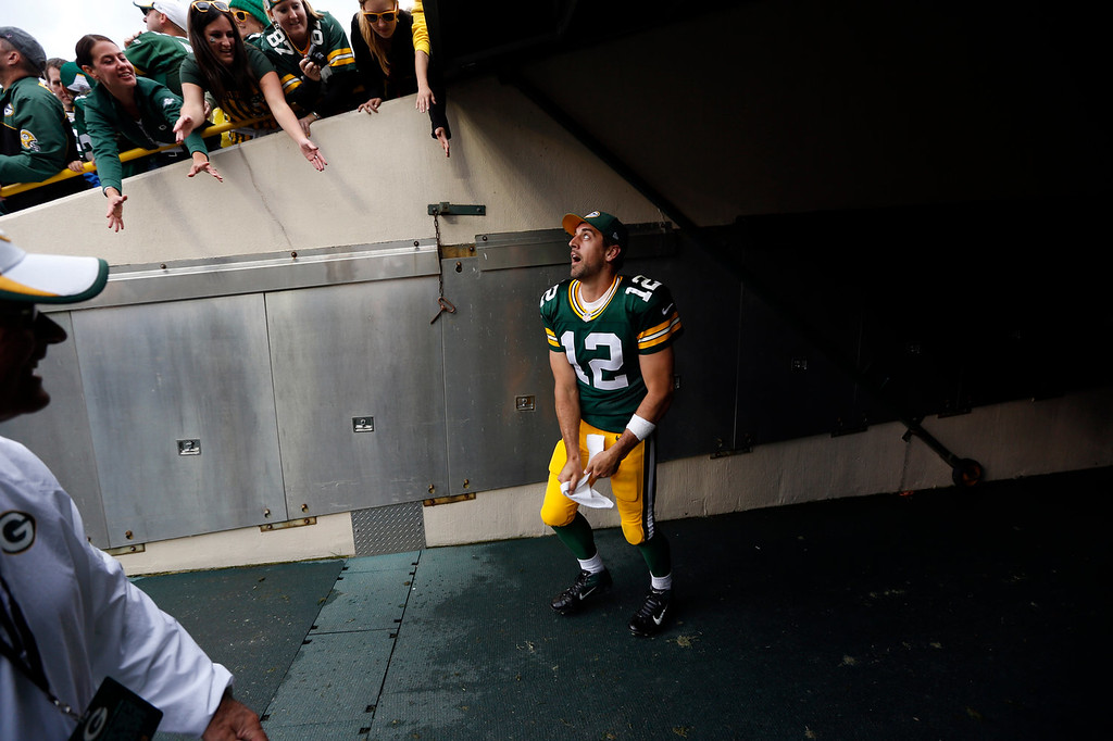 . Green Bay Packers\' Aaron Rodgers throws his towel to some fans after an NFL football game against the Washington Redskins Sunday, Sept. 15, 2013, in Green Bay, Wis. The Packers won 38-20. (AP Photo/Mike Roemer)