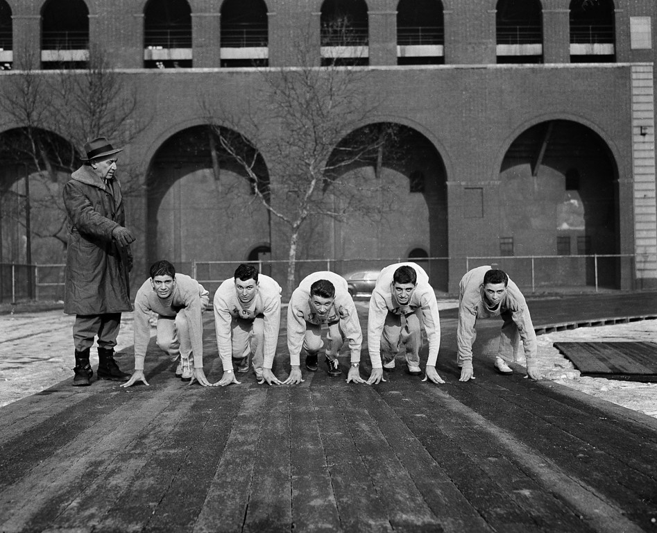 . University of Pennsylvania track coach Lawson Robertson (left) puts his first track team hopefuls on their mark for a jog around the track Jan. 18, 1944. They are, left to right: Jack Kurtzer, of New York City; Don Colosono, of New York City; Carl Stheman of Lancaster, Pa.; Roy Owens of Scranton, Pa.; and Ralph Detra, also of Lancaster. (AP Photo)