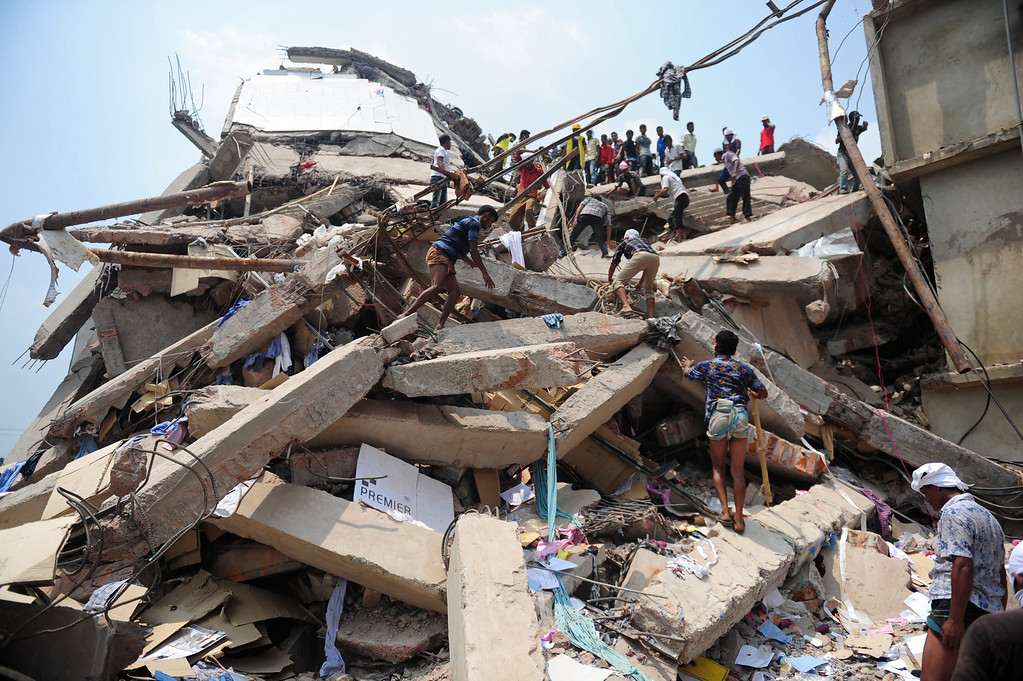 . Bangladeshi volunteers and rescue workers are pictured at the scene after an eight-storey building collapsed in Savar, on the outskirts of Dhaka, on April 25, 2013.  AFP PHOTO/Munir uz ZAMAN/AFP/Getty Images