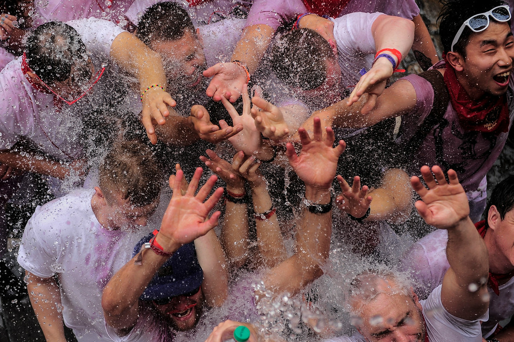 """. Revelers enjoy water being thrown from a balcony during the launch of the \'Chupinazo\' rocket, to celebrate the official opening of the 2014 San Fermin fiestas, in Pamplona, Spain, Sunday, July 6, 2014. Revelers from around the world kick off the festival with a messy party in the Pamplona town square, one day before the first of eight days of the running of the bulls glorified by Ernest Hemingway\'s 1926 novel \""""The Sun Also Rises.\"""" (AP Photo/Alvaro Barrientos)"""