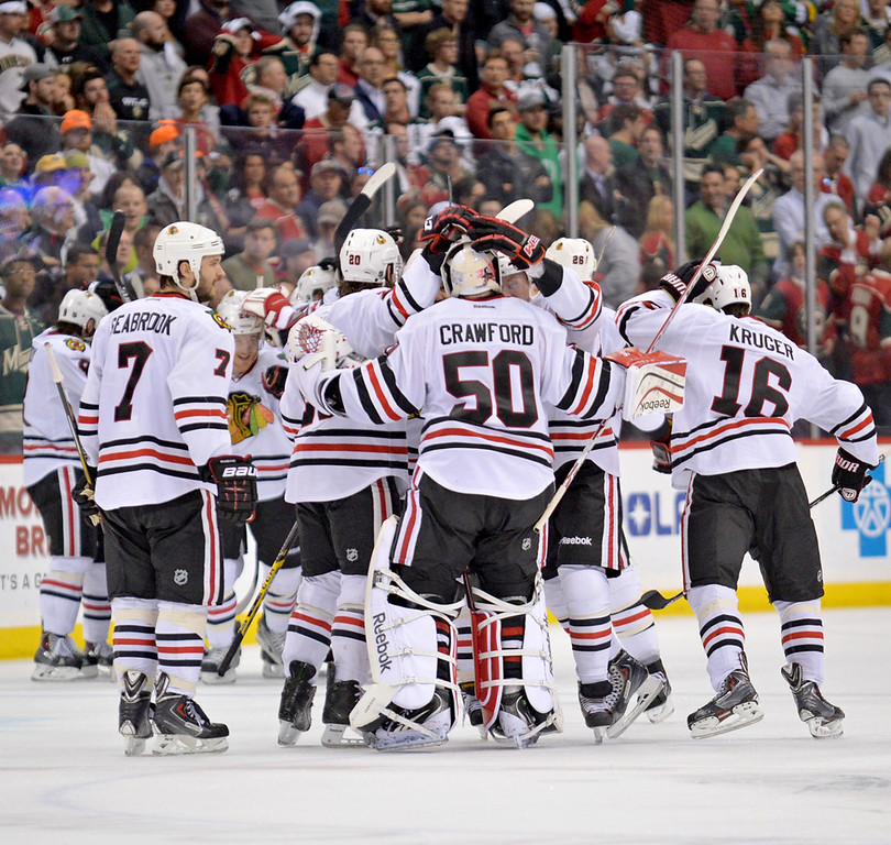 . Blackhawks players swarm goaltender Corey Crawford, who stopped 34 shots, five in the overtime period, as Chicago knocked the Minnesota Wild out of the playoffs with a 2-1 win in Game 6.  (Pioneer Press: Ben Garvin)
