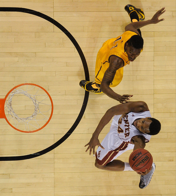 . Denver Pioneers forward Chris Udofia (34) drives past Wyoming Cowboys forward Derek Cooke Jr. (11) for a basket during the first half December 15, 2013 Magness Arena. (Photo by John Leyba/The Denver Post)
