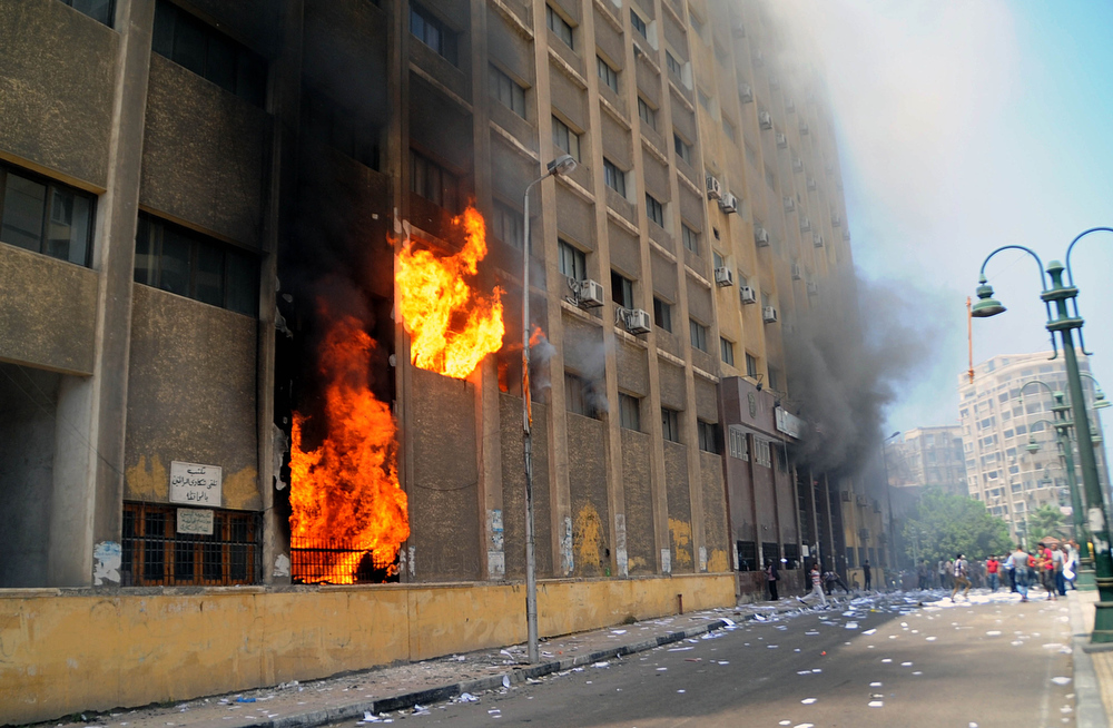 . Supporters of the Muslim Brotherhood and Egypt\'s ousted president Mohamed Morsi storm and set fire to a local council building in Egypt\'s northern coastal city of Alexandria on August 14, 2013. Clashes broke out following a demonstration against security forces clearing two pro-Morsi protest camps in Cairo. AFP PHOTO / STRSTR/AFP/Getty Images