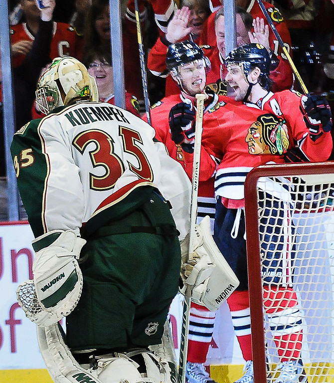 . Chicago center Patrick Sharp, right, and Chicago center Jonathan Toews celebrate Sharp\'s power play goal in the third period Minnesota goalie Darcy Kuemper, foreground, watches. (Pioneer Press: Ben Garvin)