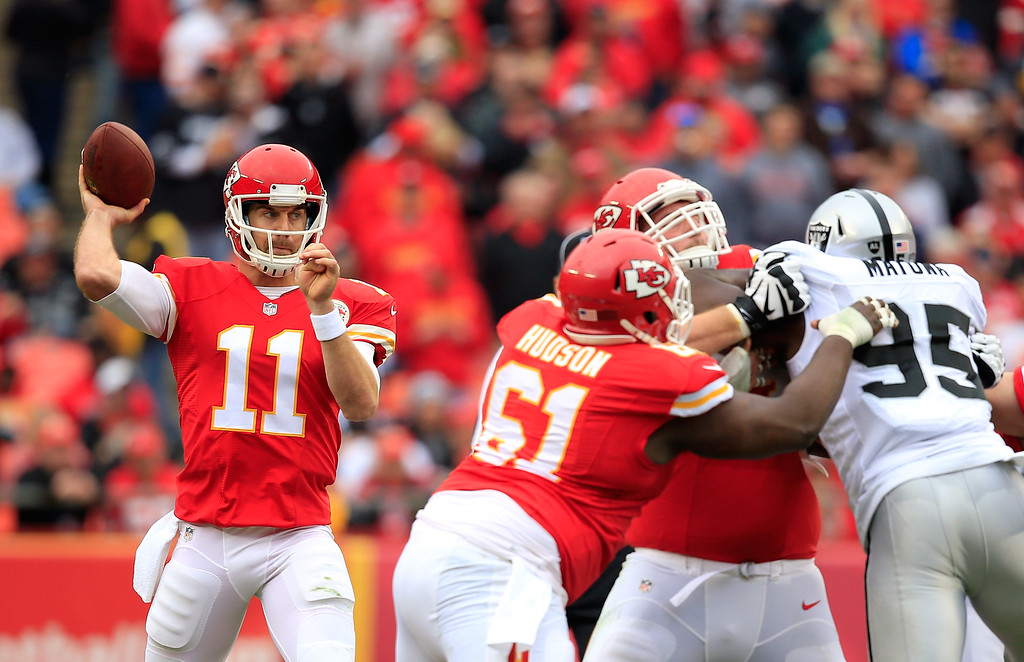 . KANSAS CITY, MO - DECEMBER 14:   Alex Smith #11 of the Kansas City Chiefs passes against the Oakland Raiders during the first half at Arrowhead Stadium on December 14, 2014 in Kansas City, Missouri.  (Photo by Jamie Squire/Getty Images)