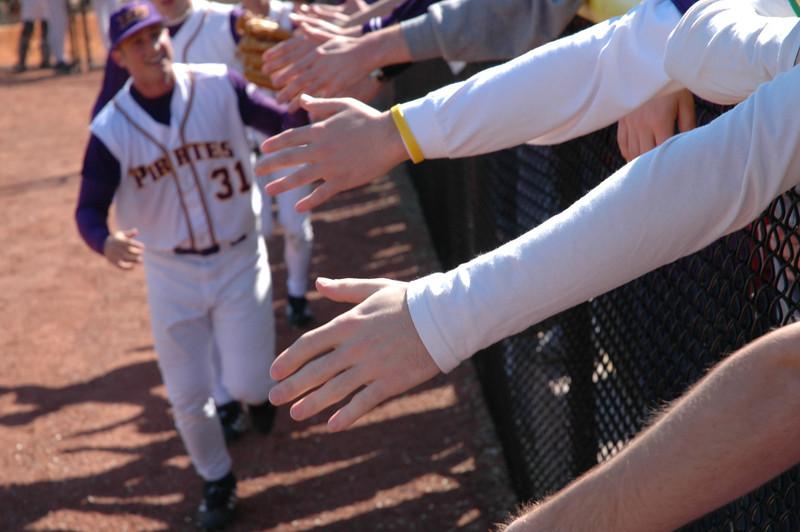 The ECU outfielders slapping hands along the left-field fense after ECU beat Michigan 2-1.