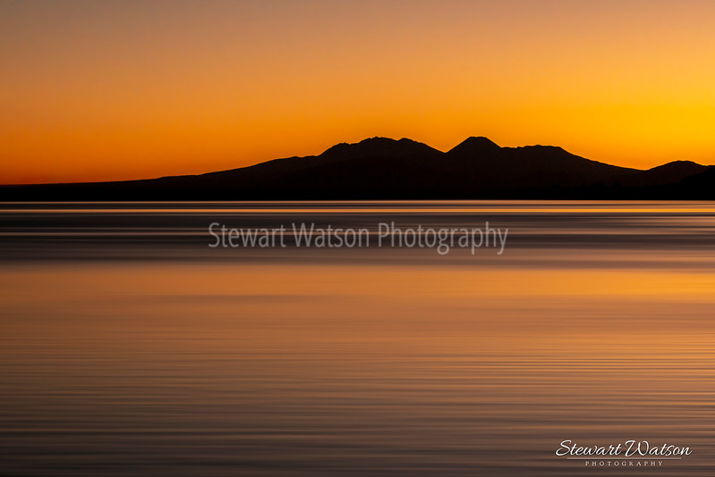 Long exposure of the Central Plateau volcanos silhouetted  above Lake Taupo as night falls