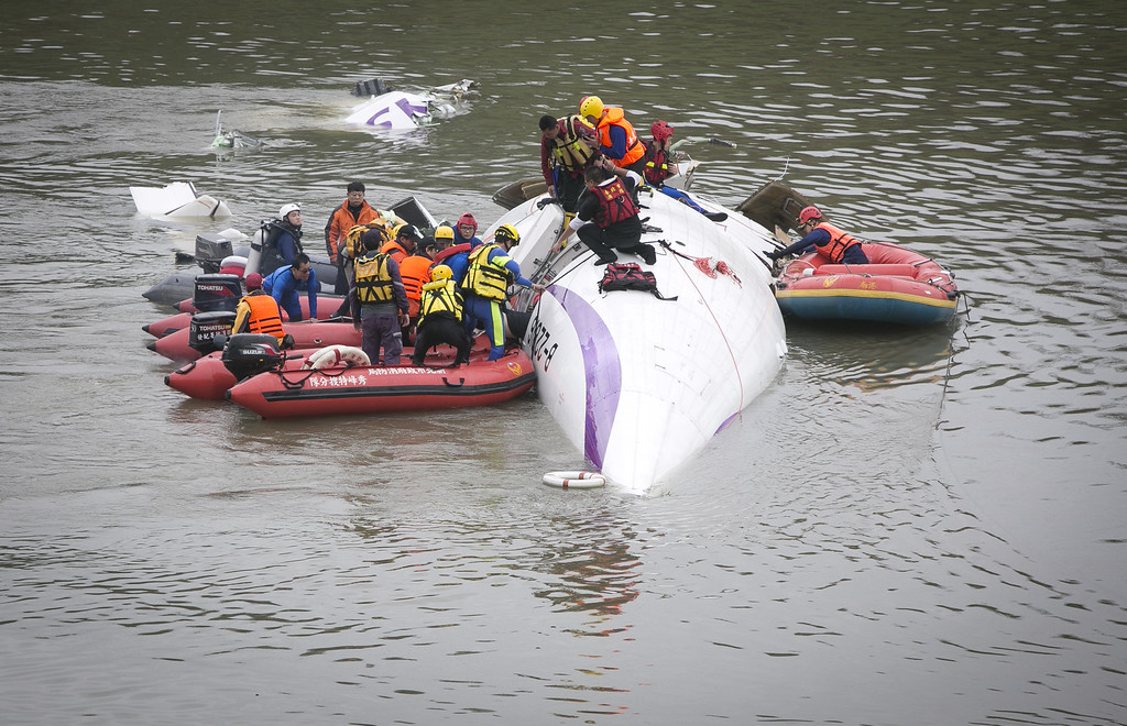 . TAIPEI, TAIWAN - FEBRUARY 04:  Rescue teams work to free people from a TransAsia Airways ATR 72-600 turboprop airplane that crashed into the Keelung River shortly after takeoff from Taipei Songshan airport on February 4, 2015 in Taipei, Taiwan.  Over 50 people were onboard the aircraft when it clipped a bridge and crashed into the river. At least two deaths have been reported. (Photo by Ashley Pon/Getty Images)