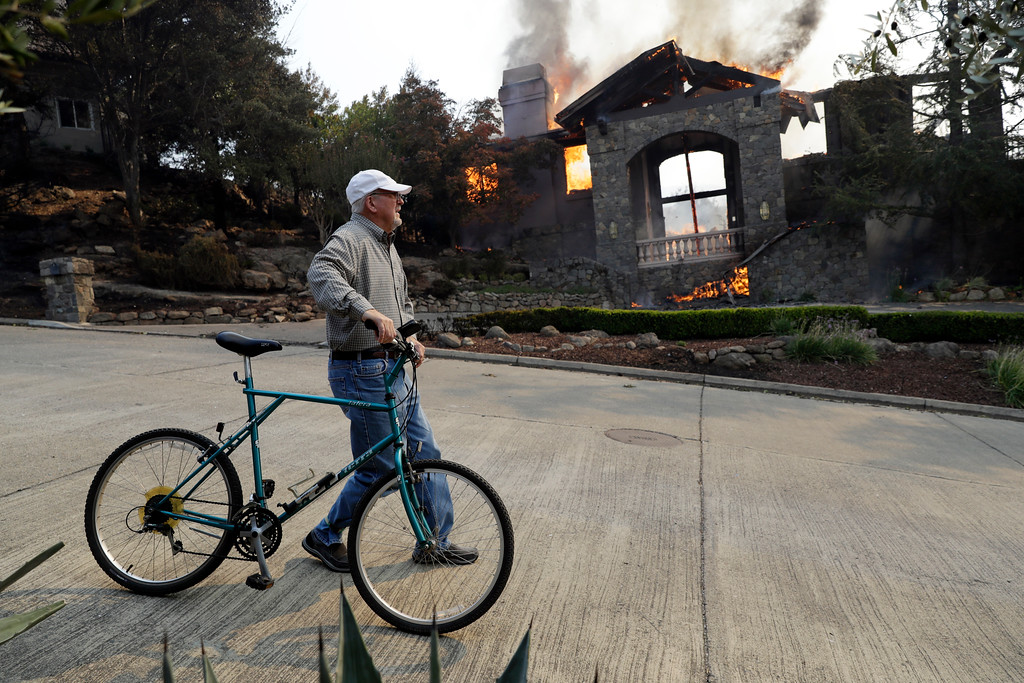 . Dean Lumbert walks past a burning house in the Silverado Crest subdivision Monday, Oct. 9, 2017, in Napa, Calif. Wildfires whipped by powerful winds swept through Northern California sending residents on a headlong flight to safety through smoke and flames as homes burned. (AP Photo/Marcio Jose Sanchez)