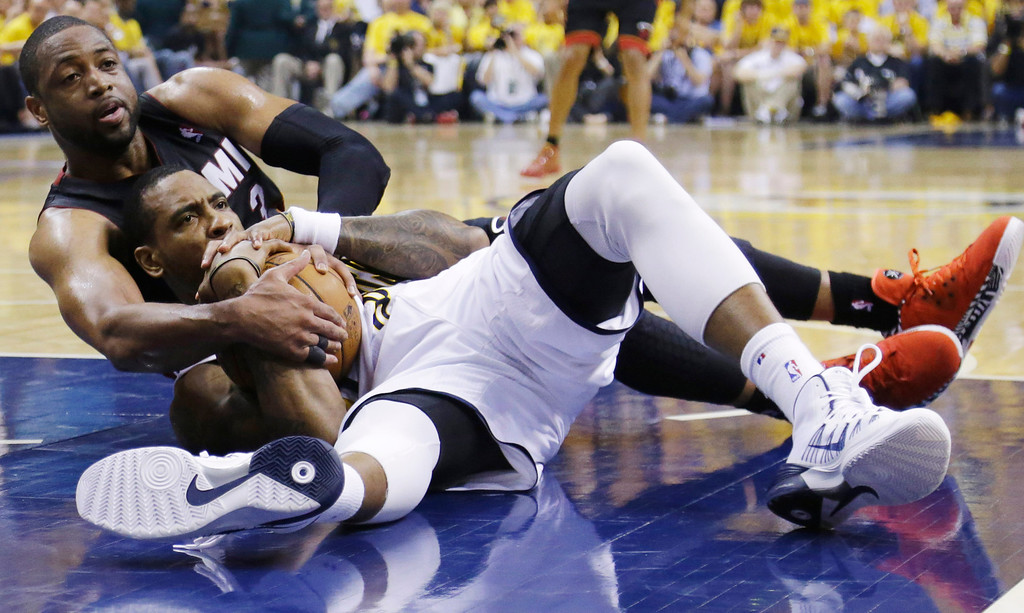 . Miami Heat guard Dwyane Wade, left, and Indiana Pacers guard Rasual Butler look for a call from an official during the first half of Game 5 of the NBA basketball Eastern Conference finals in Indianapolis, Wednesday, May 28, 2014. (AP Photo/Michael Conroy)