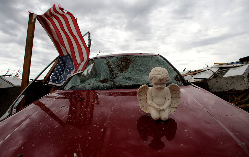 . A concrete angel rests on a destropyed car in a tornado-ravaged neighborhood Tuesday, May 21, 2013, in Moore, Okla. A huge tornado roared through the Oklahoma City suburb Monday, flattening entire neighborhoods and destroying an elementary school with a direct blow as children and teachers huddled against winds. (AP Photo/Charlie Riedel)