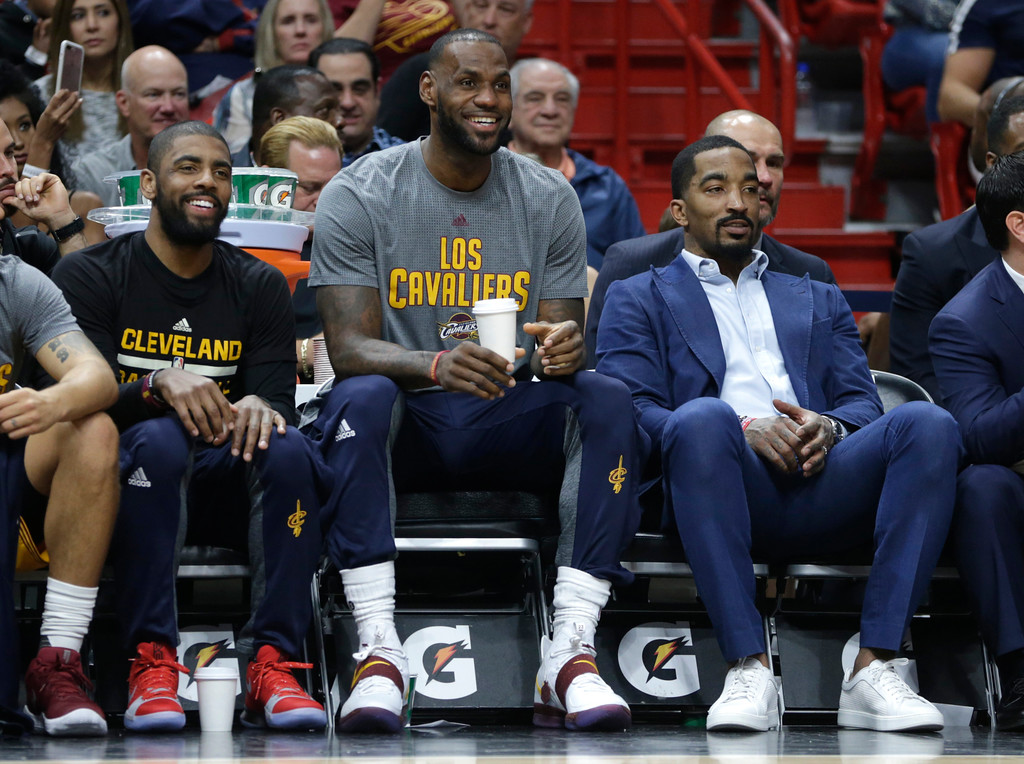 . Cleveland Cavaliers\' Kyrie Irving, left, LeBron James, center, and J.R. Smith, right, watch from the bench during the first half of an NBA basketball game against the Miami Heat, Saturday, March 4, 2017, in Miami. (AP Photo/Lynne Sladky)