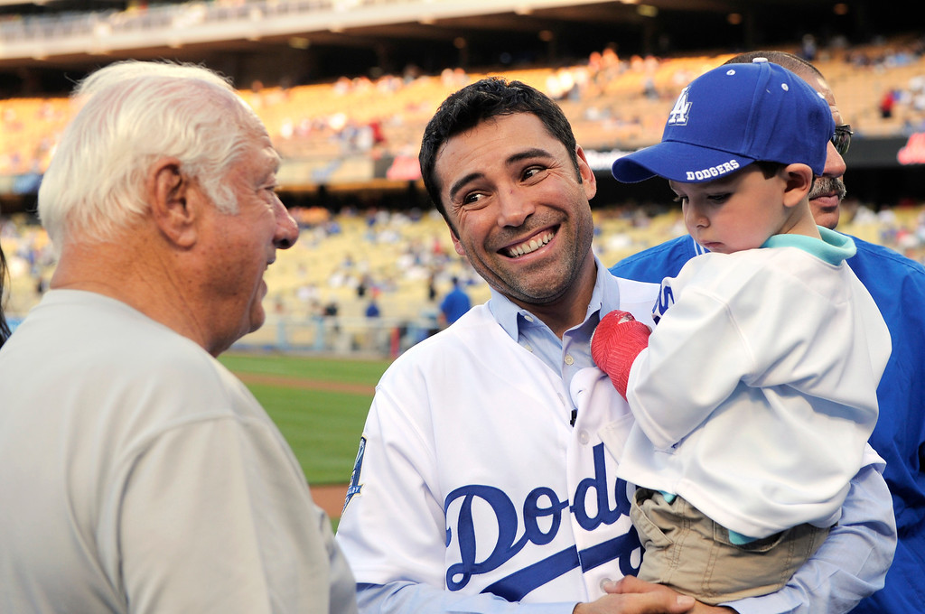 . Boxer Oscar De La Hoya talks with Dodger legend Tommy LaSorda as he holds his son Oscar, 2, prior to throwing out the ceremonial first pitch prior to the Major League Baseball game between the Los Angeles Dodgers and the Colorado Rockies, Saturday, April 26, 2008, in Los Angeles. De La Hoya is scheduled to fight Steve Forbes on May 3. (AP Photo/Mark J. Terrill)