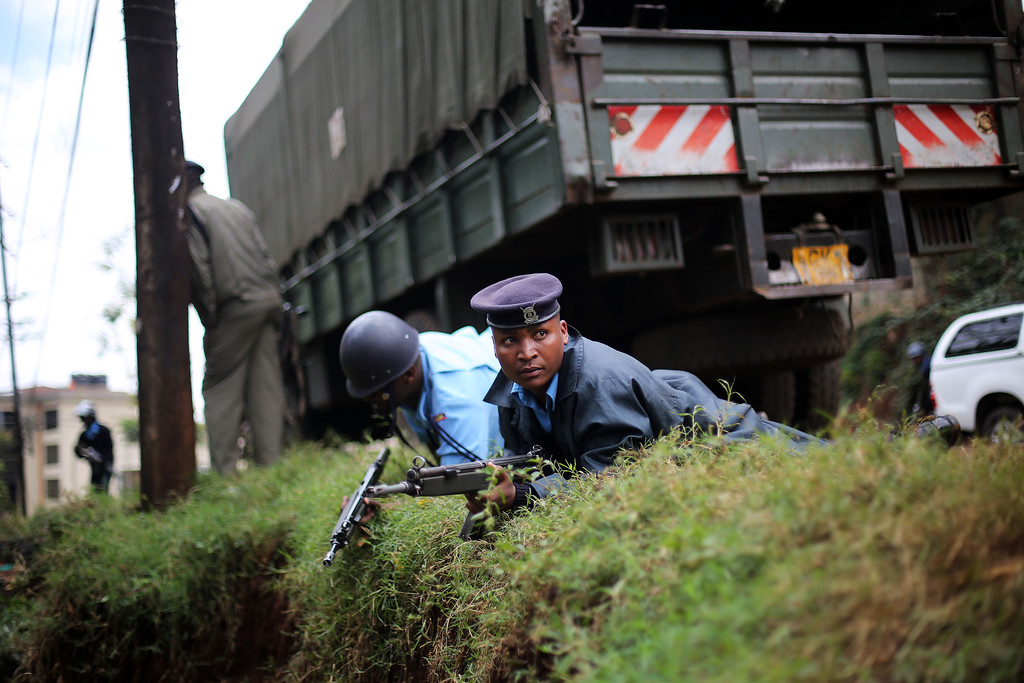 . Kenyan security officers takes cover as gunfire and explosions are heard from the Westgate Mall in Nairobi Kenya Monday Sept. 23 2013. Multiple large blasts have rocked the mall where a hostage siege is in its third day.  (AP Photo/ Jerome Delay)