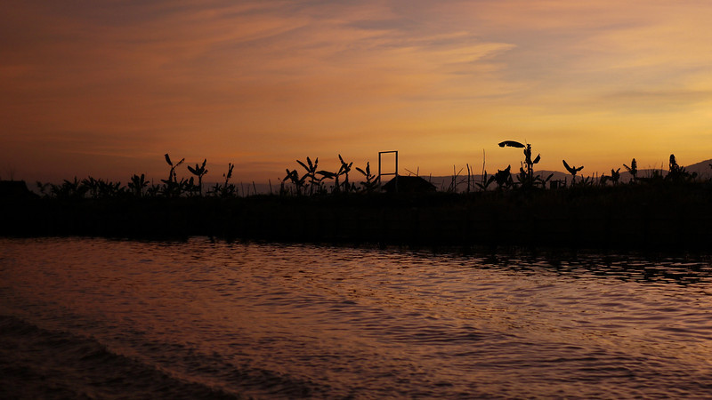 A gorgeous sunset with palms and tangerine skies over the canals around Inle Lake, Burma (Myanmar).