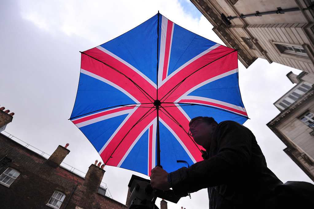 . A man holds a Union Flag umbrella as he waits opposite St James\'s Palace in central London on October 23, 2013, where Prince George of Cambridge will be baptised later in the day inside Chapel Royal.  AFP PHOTO/CARL COURT/AFP/Getty Images