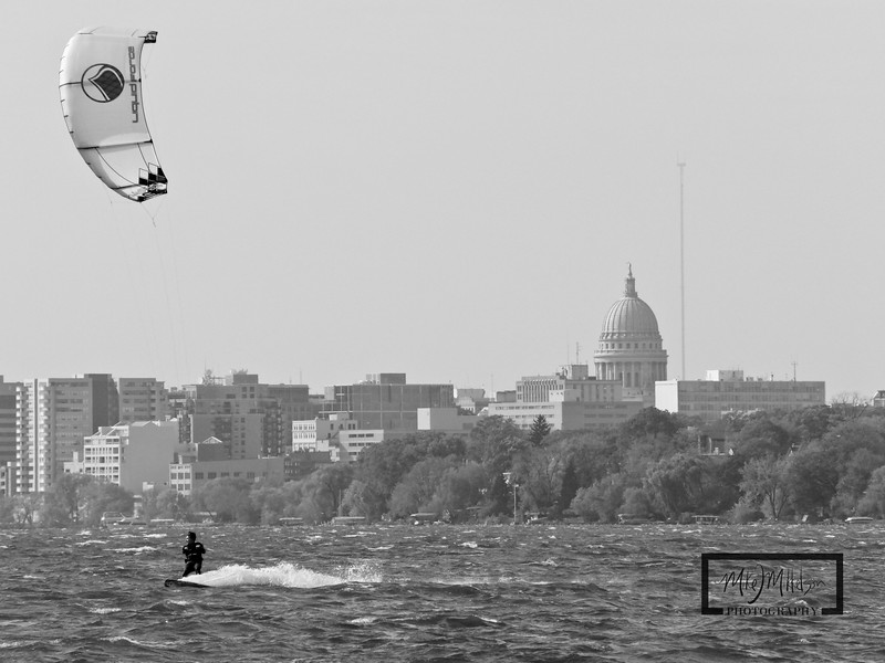 Tim Sugar Kiteboarding on Lake Monona in Madison, Wisconsin.  Capitol building and Isthmus in background.  Sailing on a 9m Liquid Force Assault.