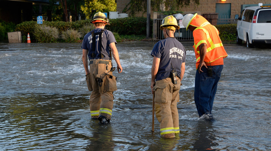 . June 17,2014. Burbank. CA. Burbank fire and city crews look for a shut off valve after a 30 inch water main broke at the Burbank Fire training center Tuesday. The water created a river in the streets that were near by the brake but did not flood any homes near by. Burbank water and power crews are on scene working to shut off the water.  Photo by Gene Blevins/LA DailyNews