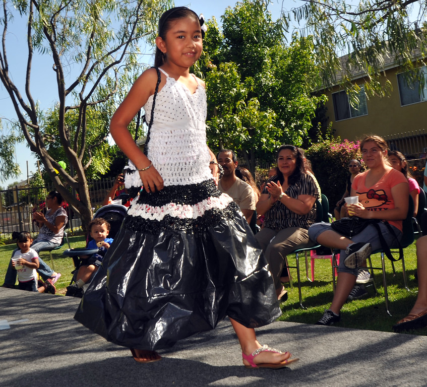 """. Melany Reynaga, 8, displays her plastic evening dress with a crocheted top and pleated plastic bag skirt in the \""""Art of Recycling\"""" showcase at the Community Resource Center in South Whittier on Thursday June 20, 2013. Students from the CRC�s Homework Assistance Program will join other local artists to showcase their wearable art made from 100% recyclable items such as newspaper, plastics, can tabs, candy wrappers, and other materials that most people toss in the trash. (SGVN/Staff Photo by Keith Durflinger)"""
