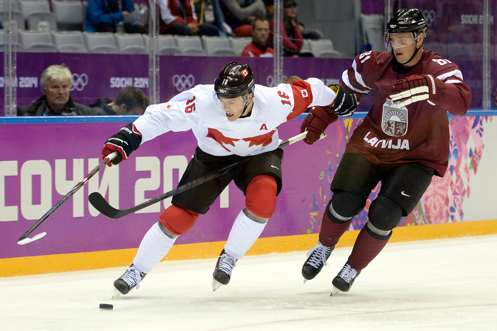 . Jonathan Toews (16) of the Canada and Georgijs Pujacs (81) of the Latvia vie for the puck during the first period of men\'s hockey action. Sochi 2014 Winter Olympics on Wednesday, February 19, 2014 at Bolshoy Ice Arena. (Photo by AAron Ontiveroz/ The Denver Post)