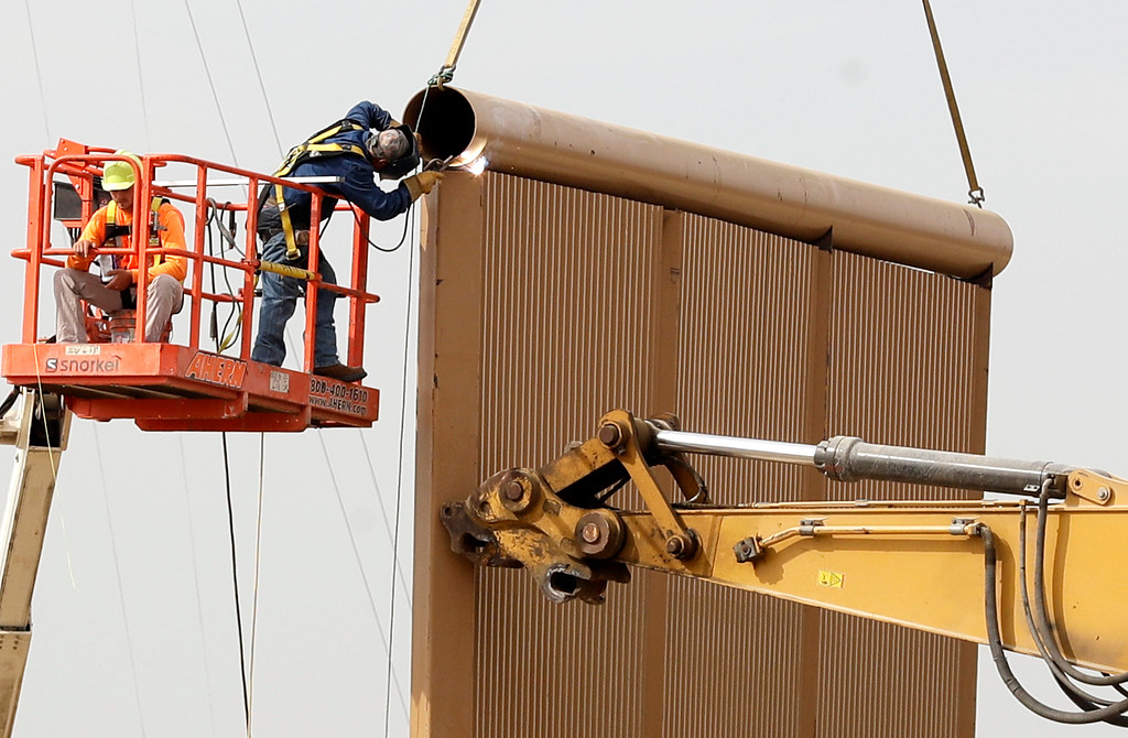 . Crews work on a border wall prototype near the border with Tijuana, Mexico, Thursday, Oct. 19, 2017, in San Diego. Companies are nearing an Oct. 26 deadline to finish building eight prototypes of President Donald Trump\'s proposed border wall with Mexico. (AP Photo/Gregory Bull)