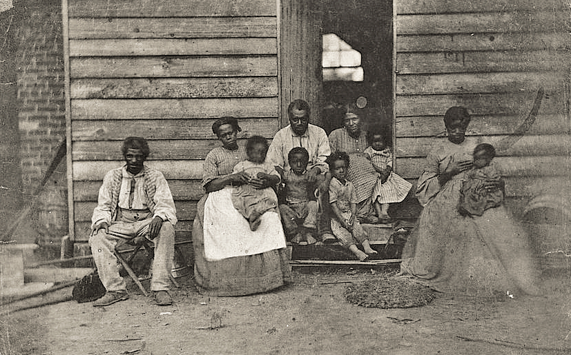 . African American slave family or families posed in front of wooden house, Washington, D.C. or Hampton, Virginia.Houghton, G. H. (George Harper), ca. 1824-1870, photographer. Library of Congress