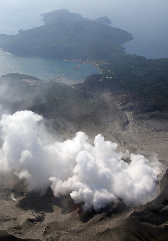 . A column of smoke raises from Mount Shindake on Kuchinoerabu island, southern Japan, Friday, May 29, 2015. The volcano erupted in spectacular fashion on the small island on Friday, spewing out rocks and sending black clouds of ash 9 kilometers (5.6 miles) into the sky. Authorities told people on the island to evacuate. (Kyodo News via AP)