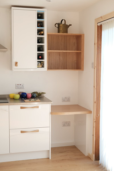 Custom made desk area with shelves above, stainless steel worktops are a bit different..