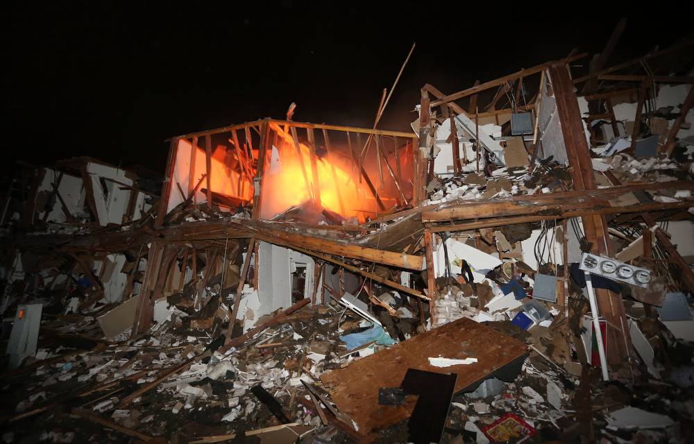 Description of . A fire still burns in a apartment complex destroyed near a fertilizer plant that exploded earlier in West, Texas, in this photo made early Thursday morning, April 18, 2013.  (AP Photo/LM Otero)